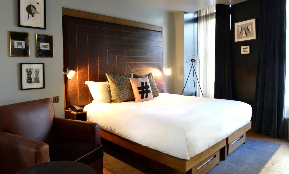 """Blick in ein geräumiges """"Roomy""""-Zimmer. Das mit dunklem Leder gepolsterte Betthaupt macht den Raum besonders gemütlich."""